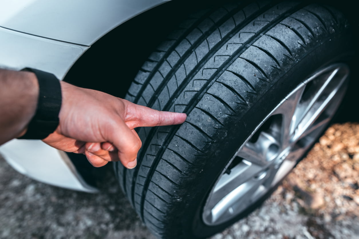 man inspecting the tread on his tire before determining if he needs to replace it