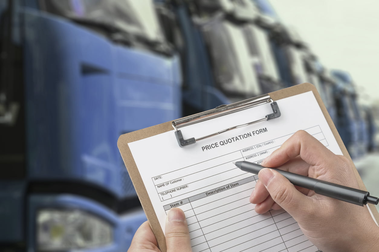 man holding auto transport quote form in front of a fleet of trucks