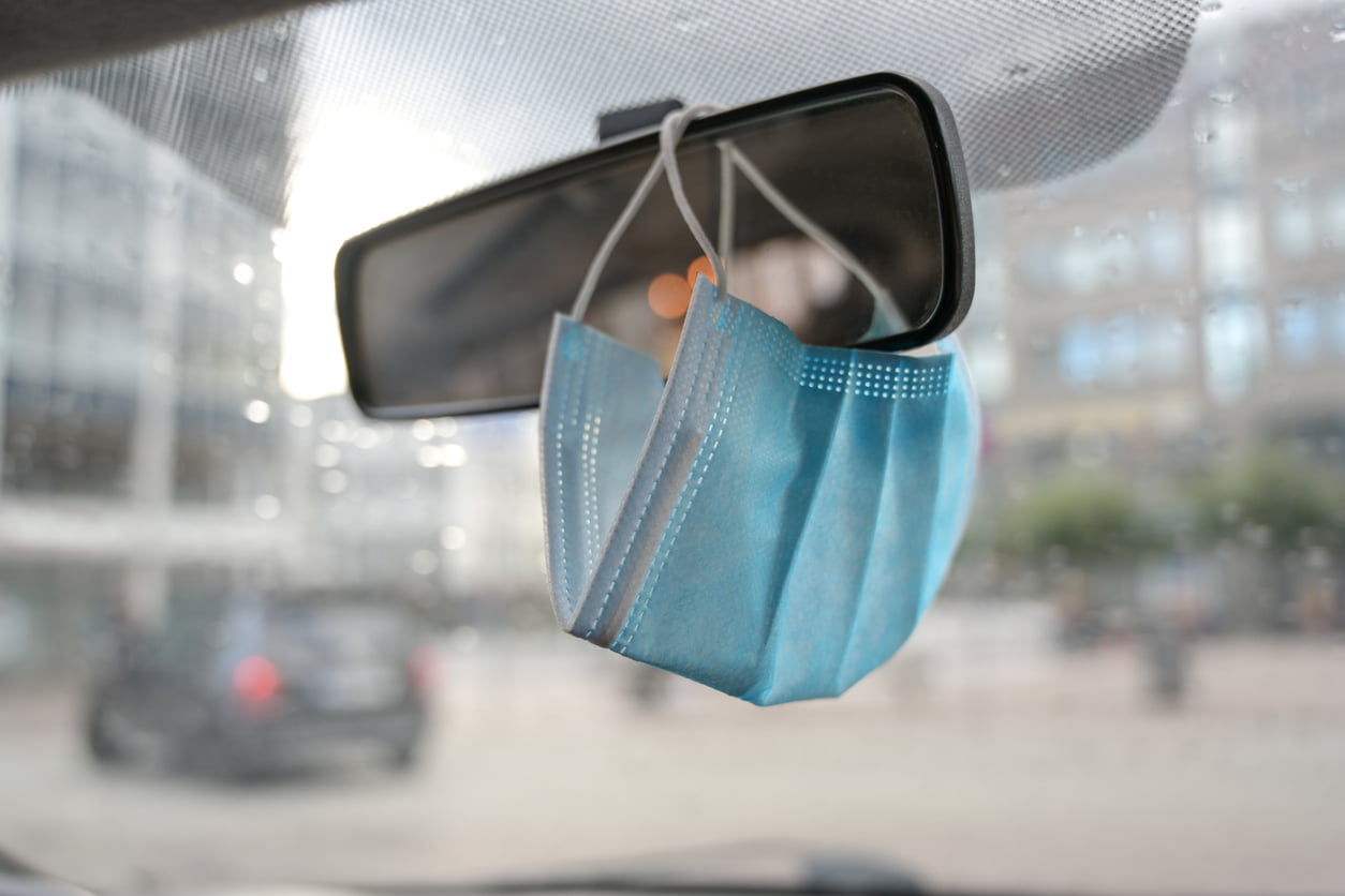 moving vehicle with medical face mask on rearview mirror