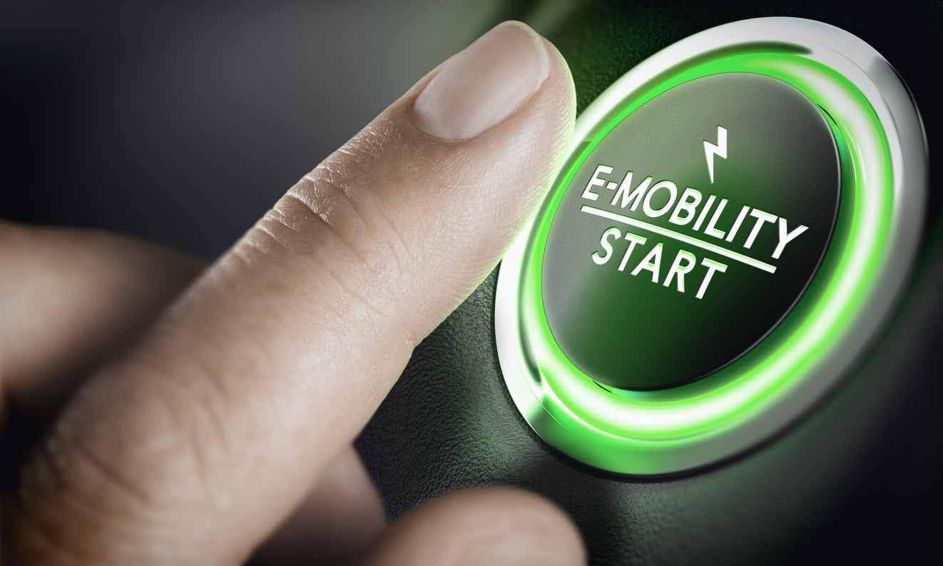 """finger over a green-lit car button labeled """"e-mobility start"""""""