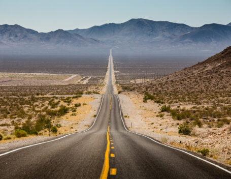 a long stretch of empty road reaching toward the mountainous horizon
