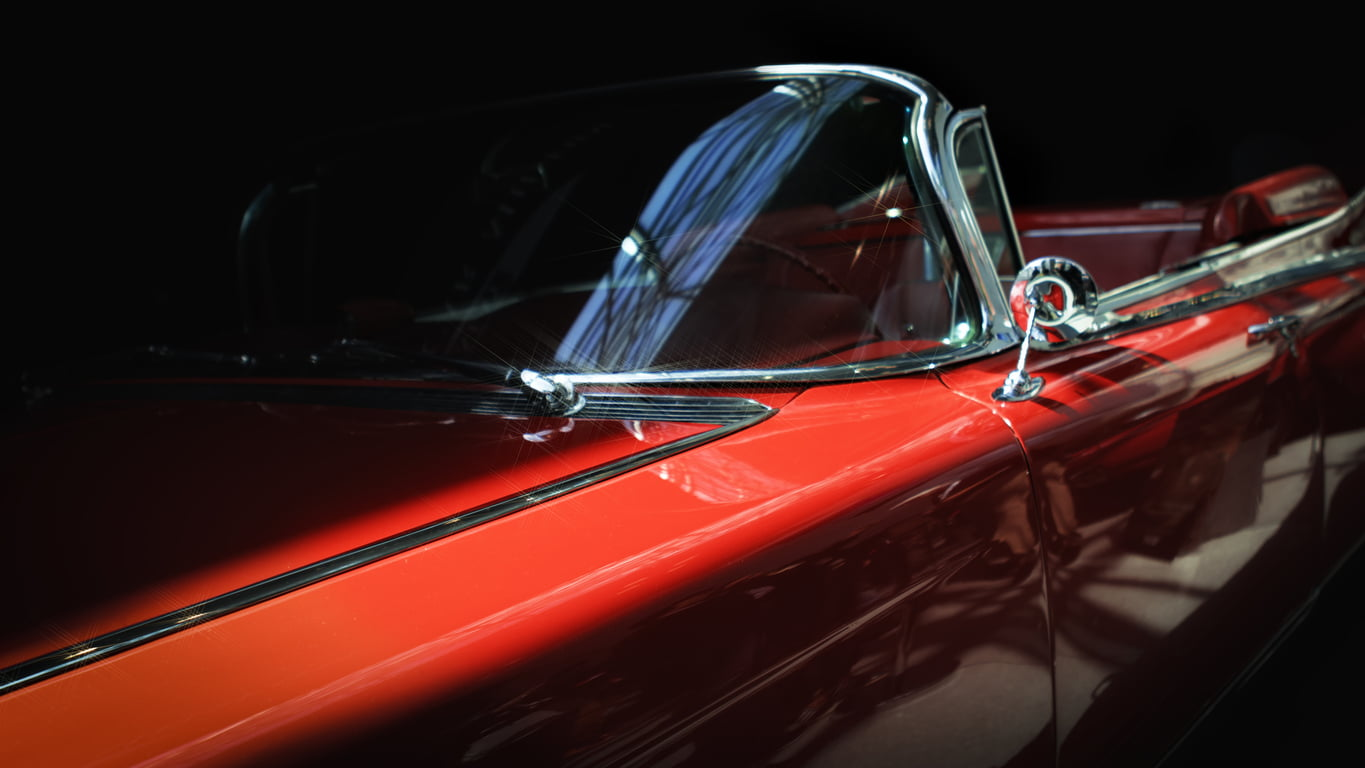 close-up of a stylish red classic car's side profile against a black background