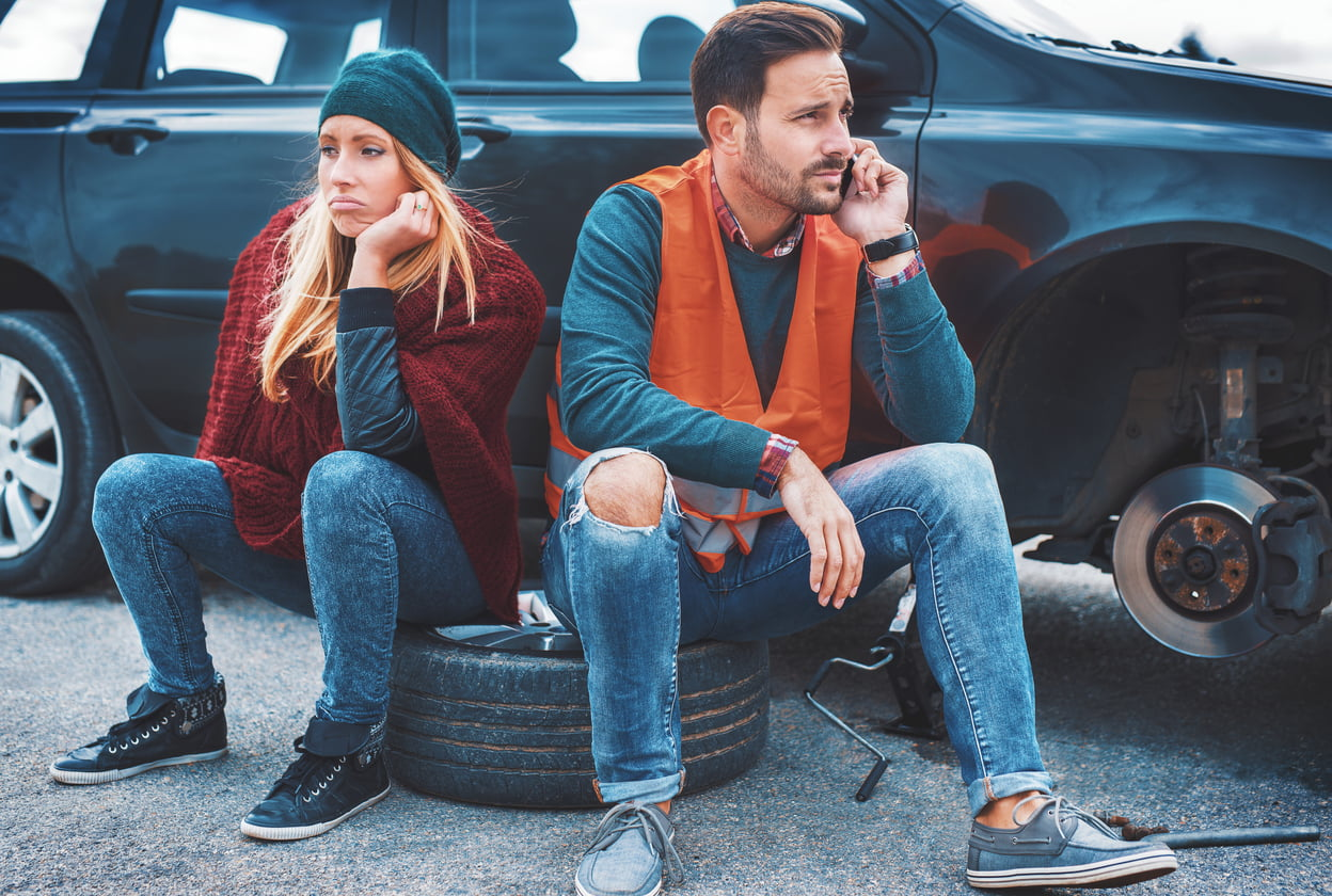 A couple on the side of the road dealing with a flat tire, one of the most common car issues you could experience.