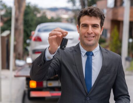 Man holding vehicle keys with car in background after the completion of a door-to-door car shipping transaction.