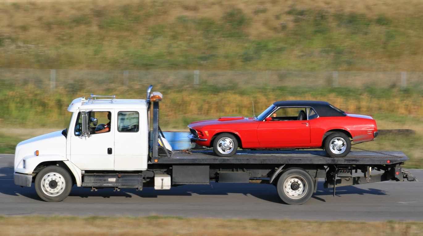 A flatbed tow truck with a classic car during the ship a non-running car process.