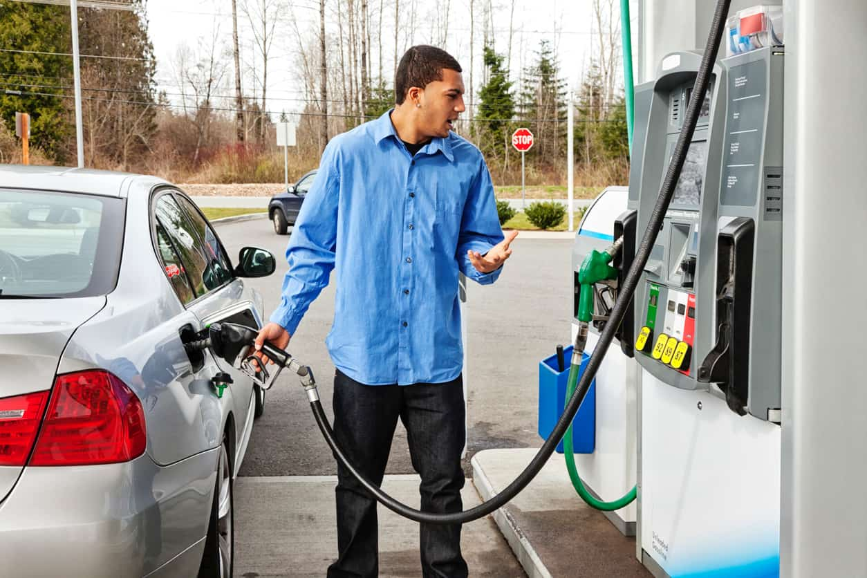 Man filling up his car while looking in disbelief at the gas prices