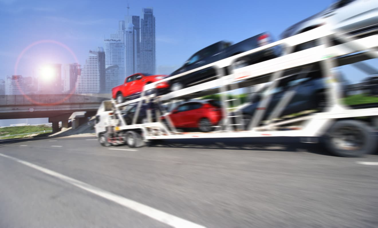Auto carrier moving quickly down a freeway in a metropolitan area